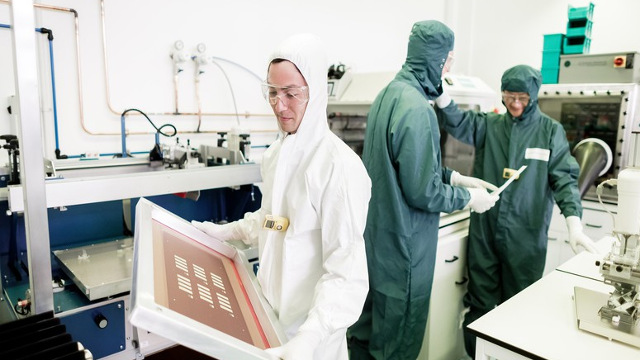Lab technicians, white and green suits in a lab